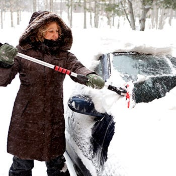 Woman Brushing Snow Off Of A Car